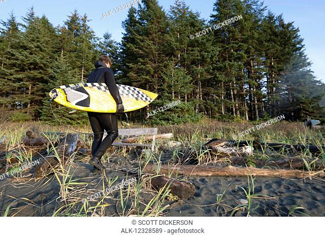 Surfer with a surfboard walking on the beach near Yakutat, Southeast Alaska; Alaska, United States of America
