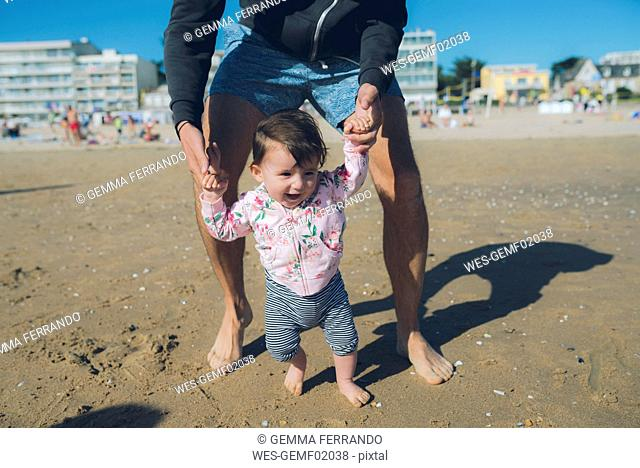 France, La Baule, baby girl learning to walk with her father on the beach
