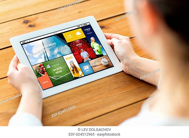 technology, people and mass media concept - close up of woman with news on tablet pc computer screen on wooden table