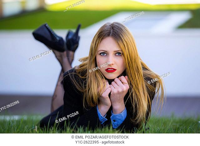 Young lady lying on meadow with crossed legs