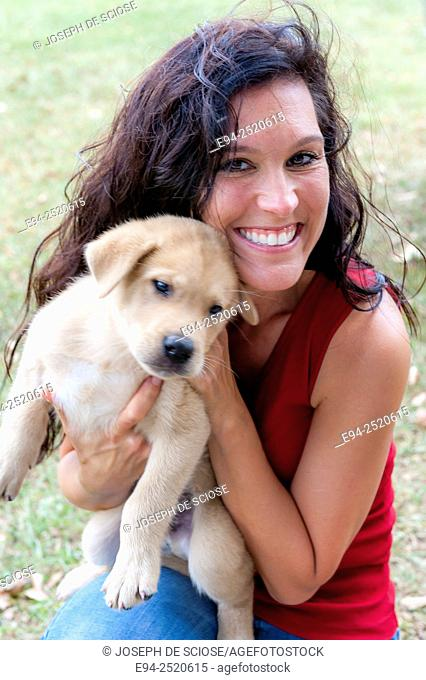 A 38 year old brunette woman holding a young puppy on a farm