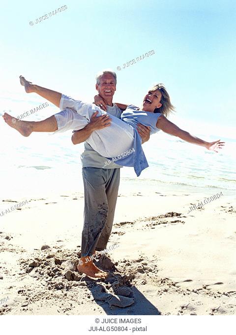 Mature man carrying woman on beach
