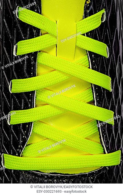 Closeup of yellow laces on black sneakers