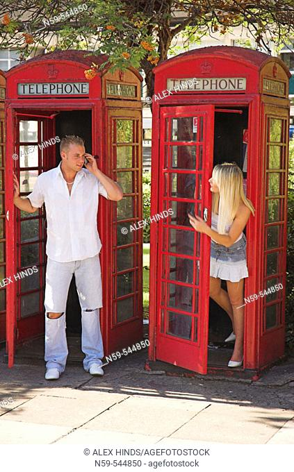 Fun young couple using mobile phones around British public phone boxes