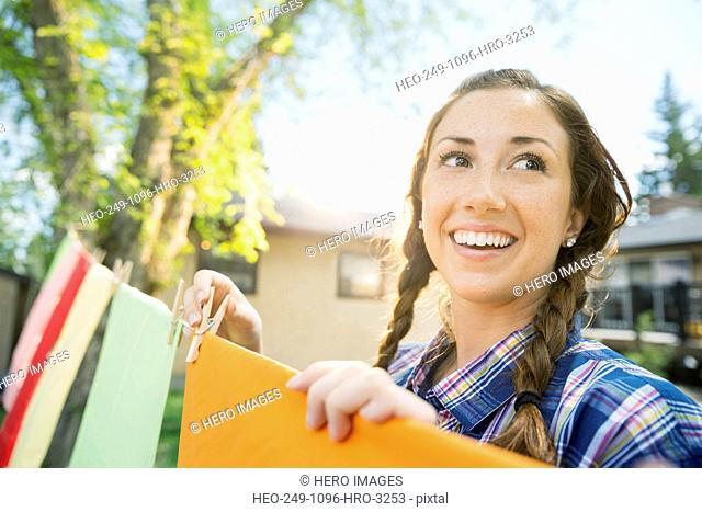 Smiling woman with braids hanging laundry on clothesline