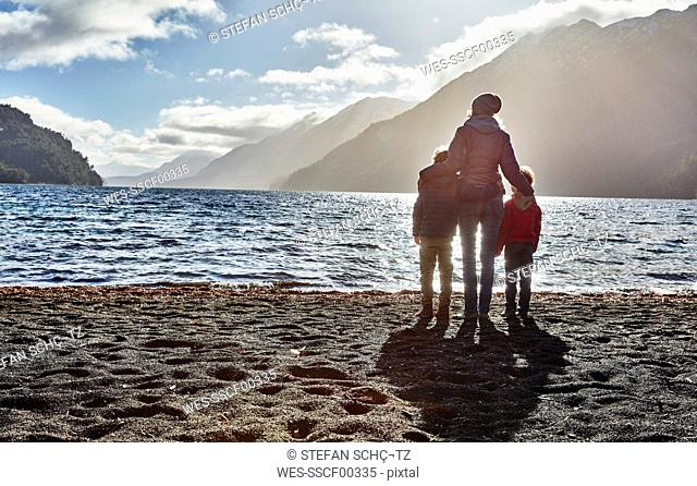 Argentina, Patagonia, Lago Nahuel Huapi, woman with two sons standing at the shore overlooking the lake