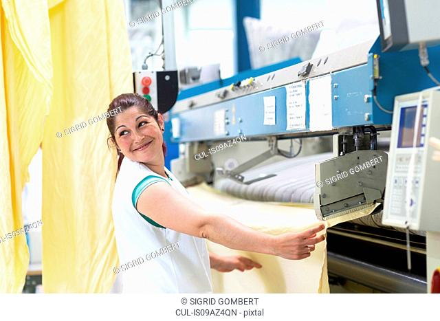 Woman in launderette using ironing machine