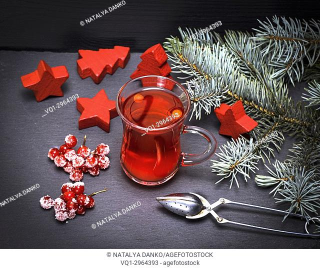 tea from fresh red viburnum in a transparent glass on a black background, top view