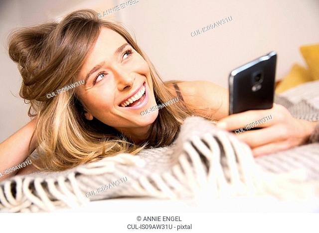 Mid adult woman lying on bed using smartphone