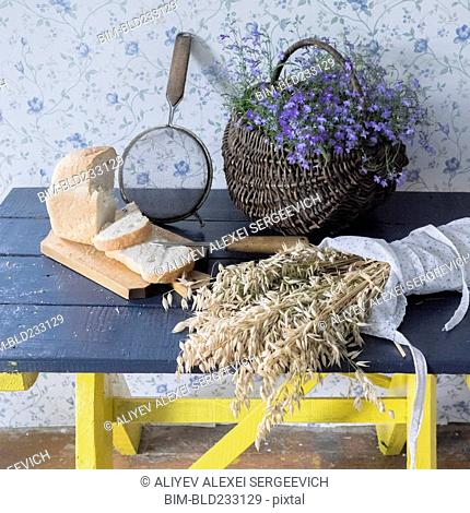 Wheat, sliced bread, sieve and flowers on bench