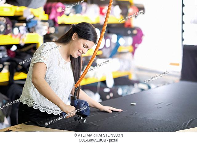 Young seamstress using cutting machine on textile at work table