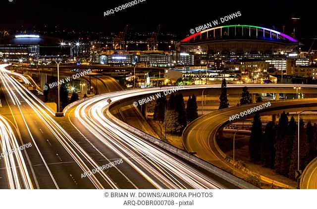 Part of the concrete jungle in Seattle, Washington. Safeco Field and a bridge, illuminated for gay pride, act as a backdrop to the busy foreground traffic
