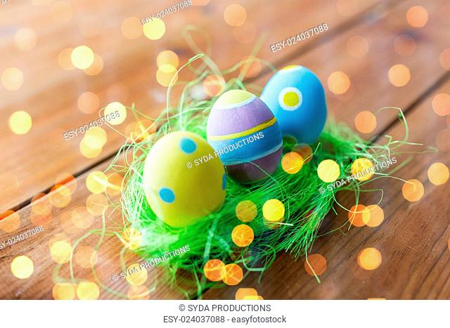 easter, holidays, tradition and object concept - close up of colored easter eggs and decorative grass on wooden surface over holidays lights
