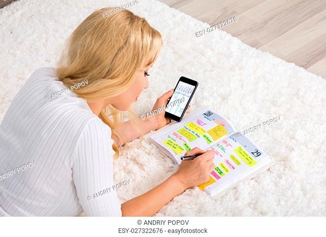 High Angle View Of Young Woman Writing Note In Diary Using Mobile Phone