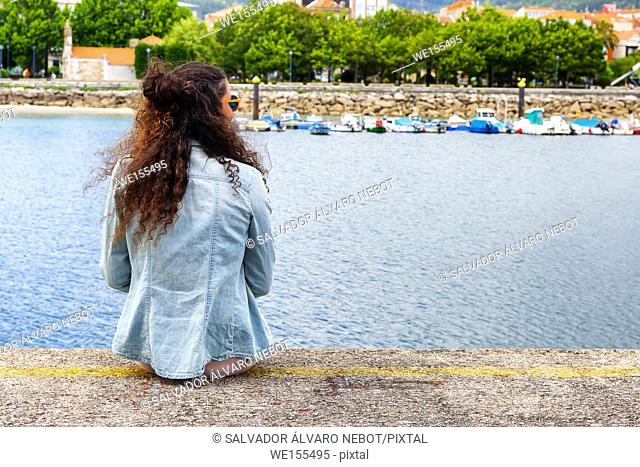 Young girl sitting in the port of Cangas de Morrazo, Pontevedra, Spain, Europe