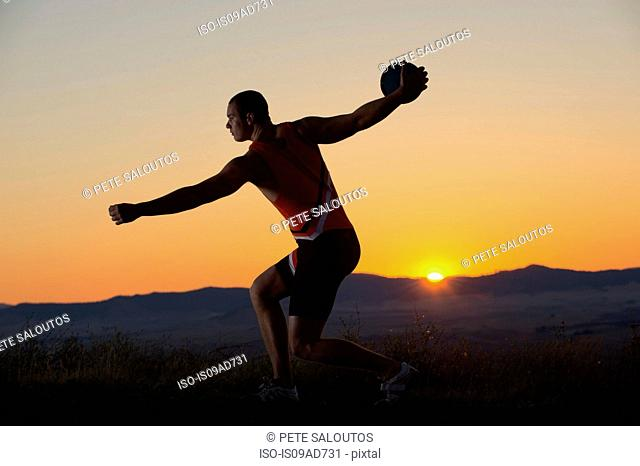 Young man preparing to throw discus at sunset