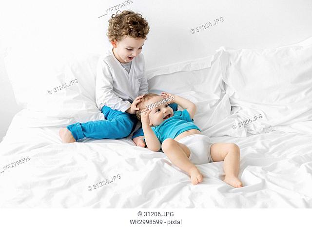 Boy wearing blue trousers sitting on a bed with a baby boy wearing blue T-shirt