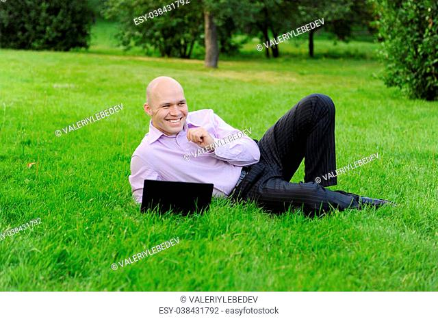 man with laptop lying on green grass in the park