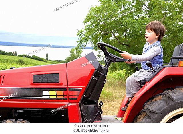 Male toddler pretending to drive tractor in garden