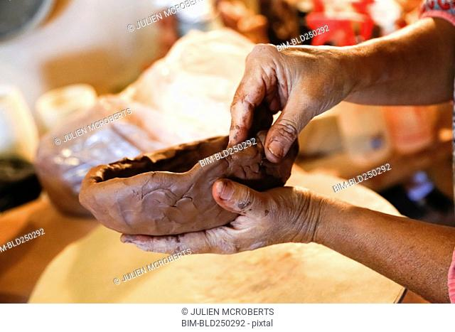 Hands of mixed race woman shaping clay in art studio