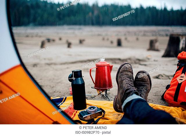Young man sitting in tent on beach, Huntington Lake, California, USA