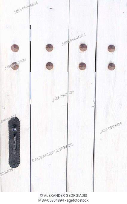 view to a white wooden door with copper rivet, Oia, Santorini, Greece