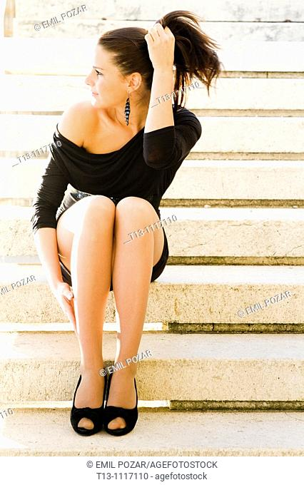 Sitting on a staircase and holding her ponytail hair