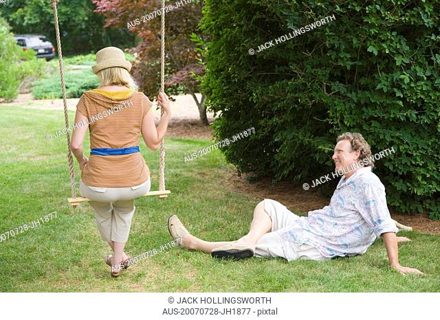 Rear view of a mid adult woman swinging on a rope swing with a mature man looking at him in a park
