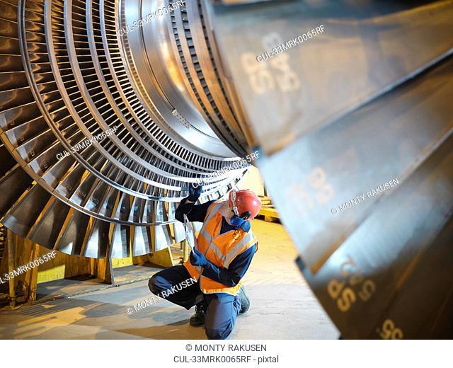 Worker inspects turbine in power station