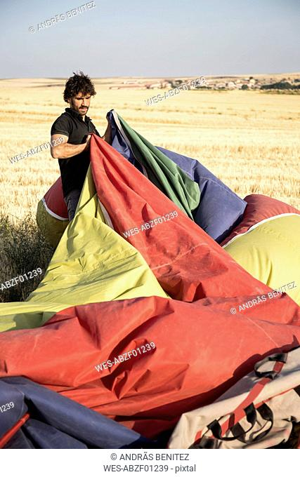 Man packing up a hot air balloon envelope