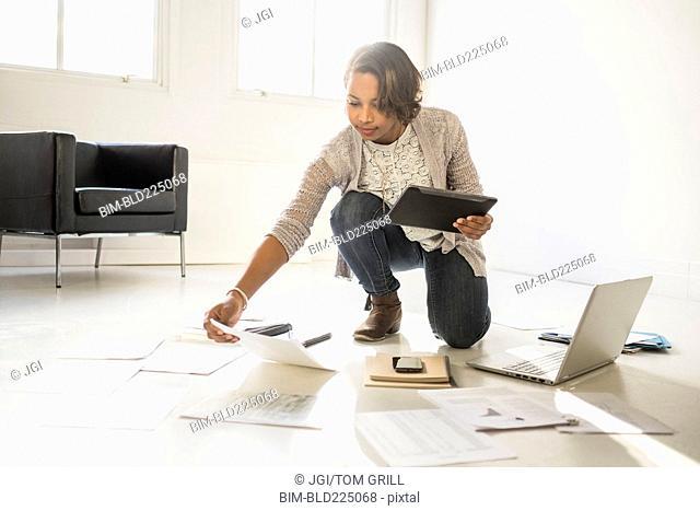 Black businesswoman using laptop and digital tablet on floor