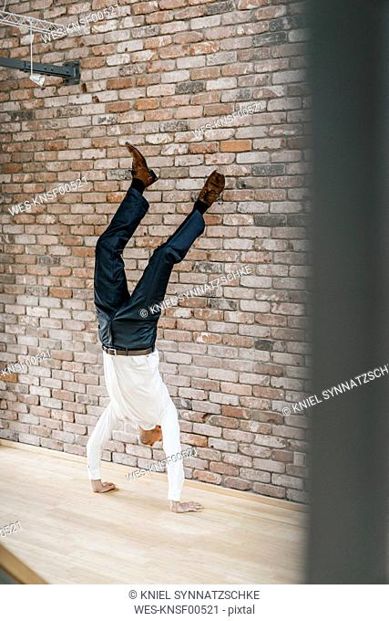 Businessman doing a handstand in front of brick wall