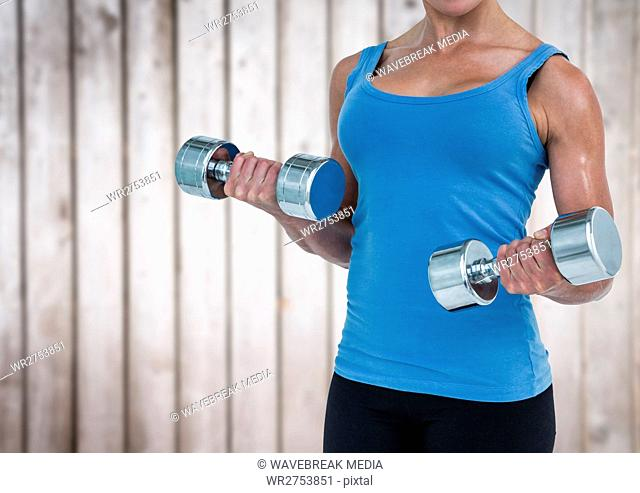 Woman weightlifting against blurry wood panel