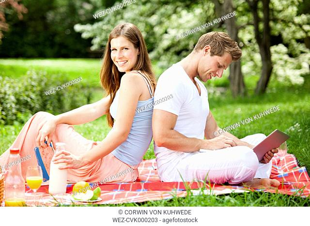 Happy couple with digital tablet having a picnic in park