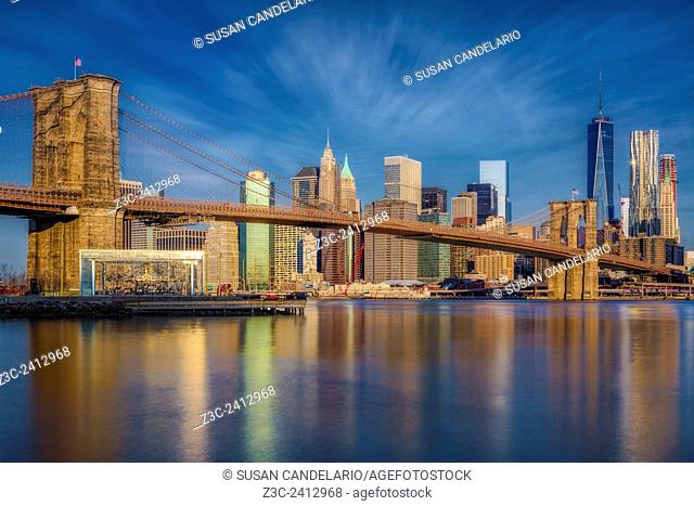 Brooklyn Bridge From Dumbo - Early morning warm light at the Brooklyn Bridge with the Manhattan skyline showcasing OneWorld Trade Center commonly referred to as...