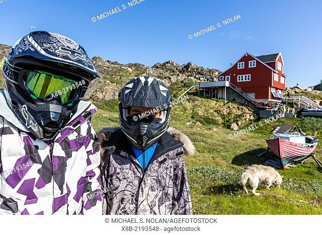 Children with motorcycle helmets and sled dog in Sisimiut, Greenland