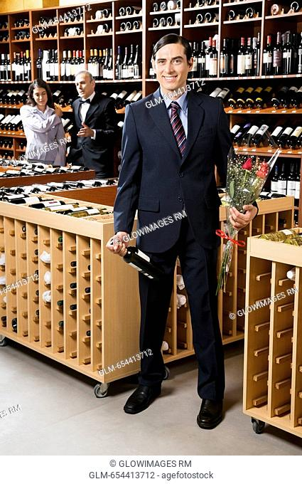 Businessman holding a wine bottle with a bouquet of flowers