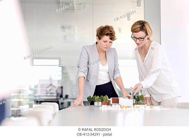 Female architects discussing model in conference room