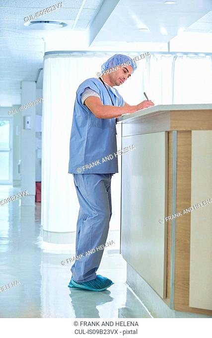 Doctor writing up medical notes at hospital nurses station