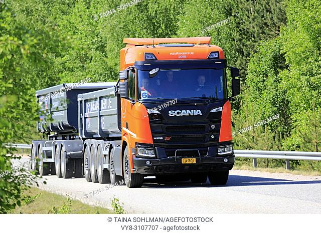 Orange Scania R650 B10X4 XT gravel truck combination on test drive on green forest road during Scania Tour 2018 in Lohja, Finland - May 25, 2018