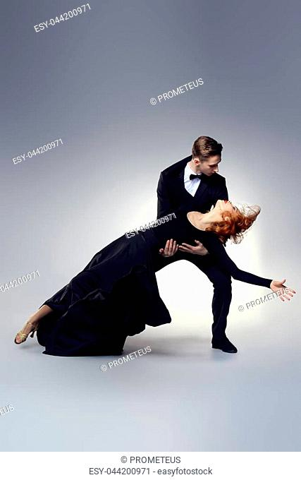 Couple of professional dancers performing tango. Beautiful young people in love dancing on a date. Studio shot