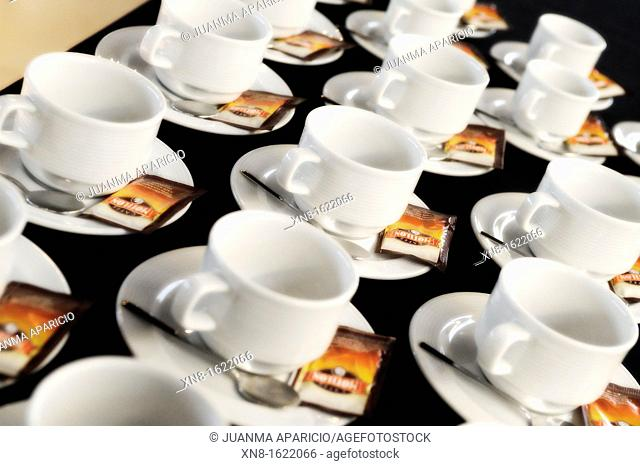 Cups, spoons and sugar sachets ready to serve coffee