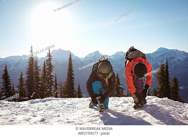 Two skier tying their shoelaces on snow covered mountain