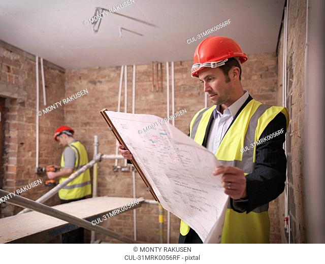 Architect with plans on building site