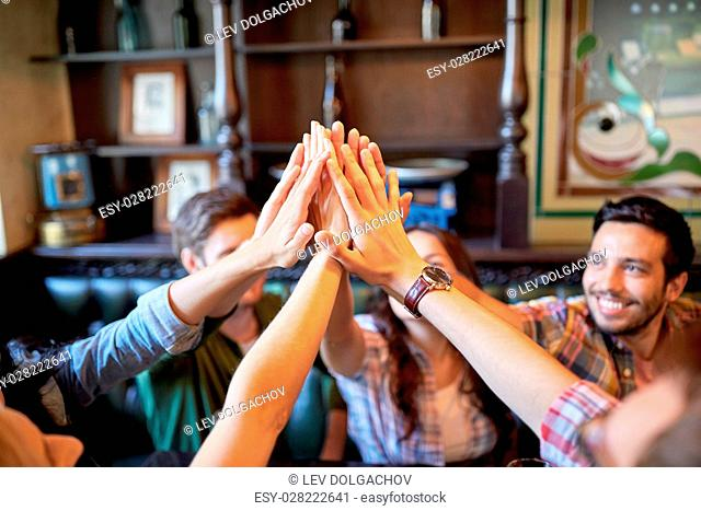 gesture, people and friendship concept - happy friends drinking beer and making high five at bar or pub