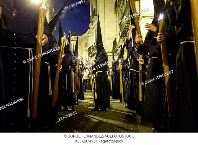 Nazarenos participating in a religious procession, with the traditional robes and hoods and carrying candles during Semana Santa (Easter) in Seville