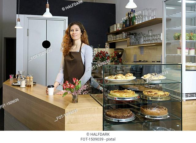 Portrait of smiling owner standing by table at cafe