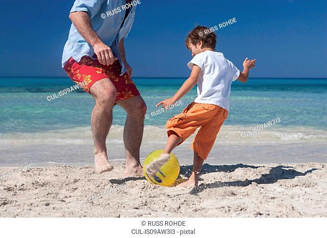 Boy playing football with father on beach, Majorca, Spain