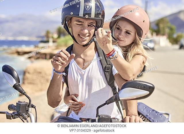 Greece, Crete, Chersonissos, couple driving quad next to coast, girlfriend stabbing sunglasses in eyes of boyfriend, eye protection, playful, teasing
