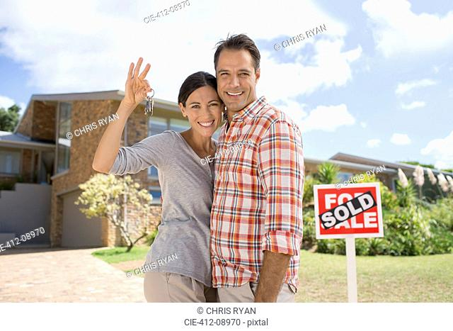 Portrait of smiling couple holding keys in front of new house